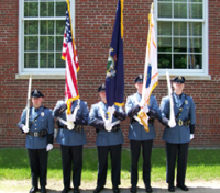 Officers in dress uniforms with flags